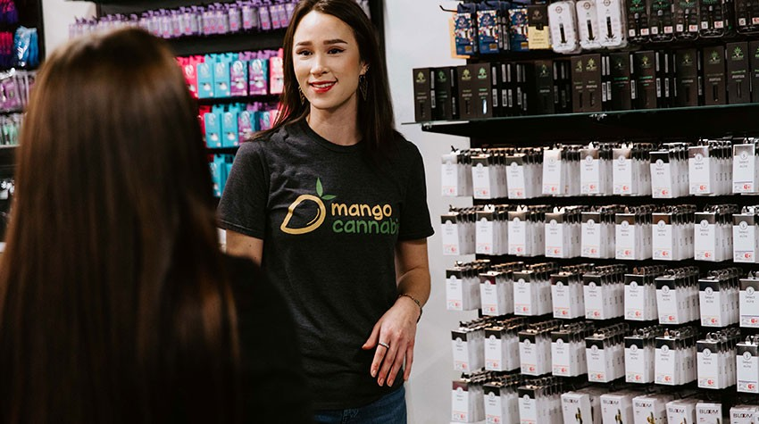 A helpful associate at Mango Cannabis assists a customer at a dispensary in Oklahoma.